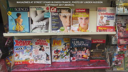 MAGAZINE COVERS AT VENDOR STAND ON PARIS STREET