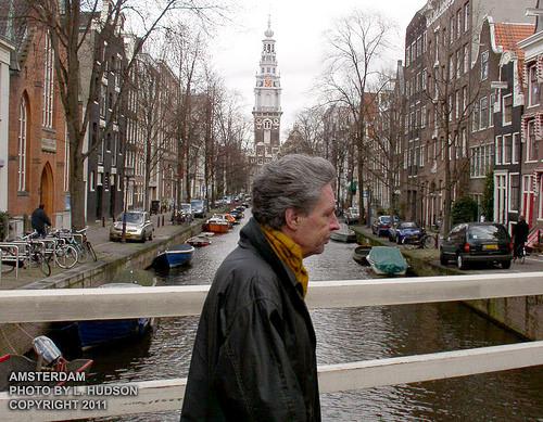 Man Walking On Amsterdam Canal Bridge