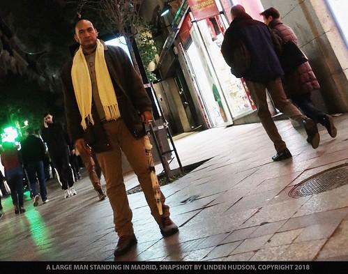 LARGE MAN STANDING - MADRID AT NIGHT