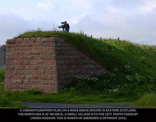 CINEMATOGRAPHER ON GRASSY MOUND - SCOTLAND